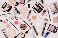 Makeup cosmetics such as eyeshadows, lipstick, mascara and makeup accessories on white, wooden background, top view stock photos