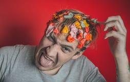 Collez dans sa tête Portrait de l'homme avec le chewing-gum dans sa tête Homme avec des cheveux couverts en nourriture photographie stock libre de droits