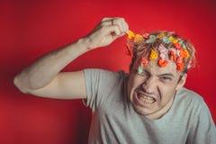 Collez dans sa tête Portrait de l'homme avec le chewing-gum dans sa tête Homme avec des cheveux couverts en nourriture photos stock