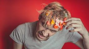Collez dans sa tête Portrait de l'homme avec le chewing-gum dans sa tête Homme avec des cheveux couverts en nourriture images libres de droits