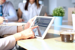 Collègues d'affaires travaillant ensemble et analysant les chiffres financiers sur un comprimé numérique Photographie stock