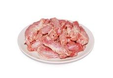 Colli freschi crudi delle frattaglie del pollo su un piatto contro fondo bianco Fotografia Stock