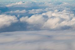 Colliding of Clouds. Rolling fluffy clouds coming together to for a cloud blanket in the blue sky Royalty Free Stock Images
