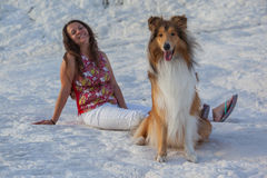 Collie dog infront of sitting young girl on white rock Stock Photography