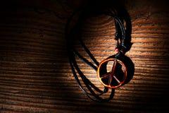 Collier avec le symbole de paix en bois sur le fond en bois Photos libres de droits