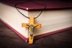 Collier croisé en bois chrétien sur la Sainte Bible photographie stock