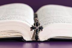 Collier croisé sur la Sainte Bible ouverte Photographie stock