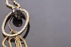 Collier d'or avec une pierre gemme noire Photographie stock libre de droits