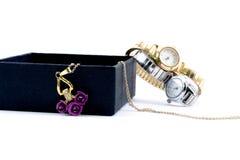 Collier d'or dans une boîte et des deux belles montres Photos stock