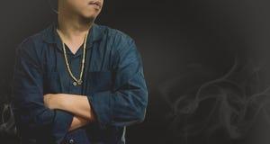 Collier d'or de vêtements pour hommes dans le support bleu de chemise devant la fumée avec le fond noir clair image libre de droits