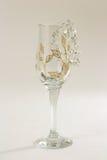 Collier de diamants dans un gobelet en verre vide sur un fond blanc Image stock
