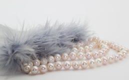 Collier de perle avec des plumes d'isolement sur le blanc Photographie stock