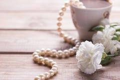 Collier de tasse et fleurs blanches Photos stock