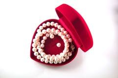Collier des perles dans une boîte rouge en forme de coeur Images libres de droits
