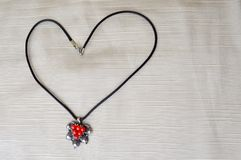 Collier du ` s de femmes avec un pendant argenté avec les cercles rouges sous forme de coeur au jour de St Valentine fait de fil  Photos libres de droits