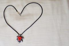 Collier du ` s de femmes avec un pendant argenté avec les cercles rouges sous forme de coeur fait de fil noir Images libres de droits