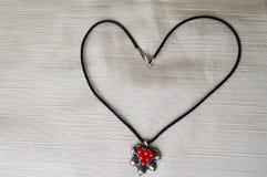 Collier du ` s de femmes avec un pendant argenté avec les cercles rouges sous forme de coeur fait de fil noir Images stock