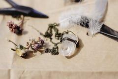 Collier en cristal, plume, et fleurs sèches sur le fond de métier photo stock
