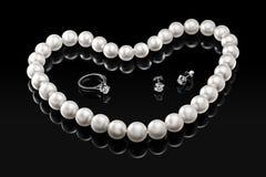 Collier et bijoux blancs réglés de perle de luxe avec des diamants dans l'anneau et des boucles d'oreille sur un fond noir Photos stock