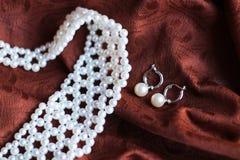 Collier et boucles d'oreille de perle sur le fond foncé photographie stock