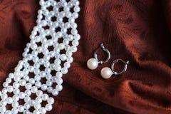 Collier et boucles d'oreille de perle sur le fond foncé image libre de droits