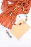 Collier et boucles d'oreille des pierres naturelles sur un fond blanc avec le rouge à lèvres rouge d'enveloppe d'écharpe Images stock