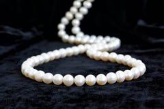 Collier pâle naturel de perle sur un velours noir Photos stock
