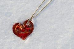 Collier rouge de coeur dans la neige Image libre de droits
