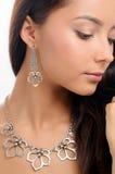 Collier sur le cou du ` s de femme et boucle d'oreille élégante sur le fond blanc Image libre de droits