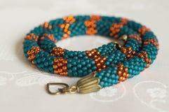 Collier tricoté des perles de couleur verte et orange Photos stock