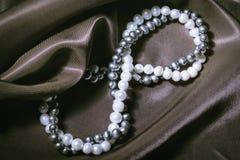 Colliers de perle naturelle sur le fond en soie Photographie stock