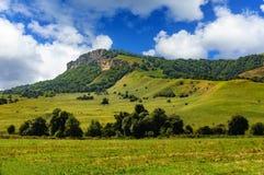 Collina dell'erba verde e cielo nuvoloso Fotografia Stock