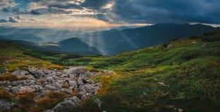 Collina della montagna con il cielo ed il raggio di sole tempestosi al tramonto Fotografia Stock Libera da Diritti