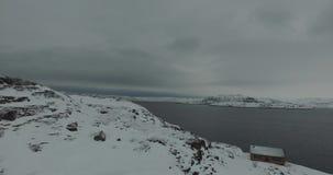 Collina della neve con la casa al piede dalla baia non gelata sotto il cielo grigio stock footage