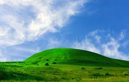 Collina e cielo blu dell'erba verde Fotografie Stock