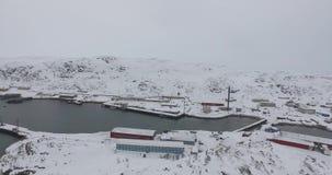 Colline basse e case della neve alla baia non gelata del mare sotto il cielo grigio video d archivio