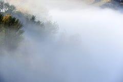 Colline dans le brouillard et les nuages brumeux de lever de soleil photos stock