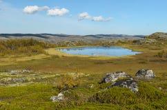Colline, tundra e lago e nuvole nel cielo blu Immagini Stock Libere da Diritti