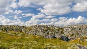 Colline, tundra, rocce e cielo con le nuvole bianche Immagine Stock