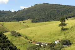 Colline verdi con la casa dell'azienda agricola immagine stock