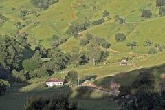 Colline verdi con la casa dell'azienda agricola fotografia stock