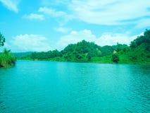 Colline verdi vicino al lago blu con il bello cielo fotografia stock