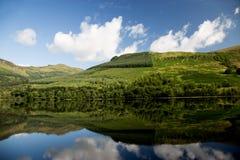 Collines boisées et réflexions dans un loch écossais Images stock