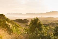 Collines brumeuses dans la lumière orange de coucher du soleil Image libre de droits