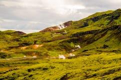 Collines de mousse et caloducs verts près de centrale géothermique de Nesjavellir en Islande Images stock