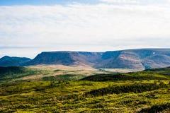 Collines vertes avec la forêt contre le plateau sous le ciel nuageux Images stock