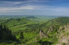Collines vertes en vallée de montagne et ciel nuageux Photo stock