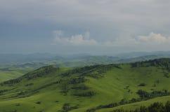 Collines vertes en vallée de montagne et ciel nuageux Image libre de droits