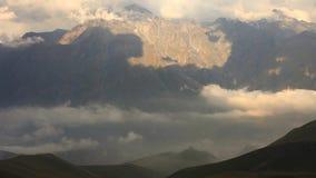 Collines vertes et montagnes de Caucase au beau coucher du soleil nuageux L'église de Gergeti sur le fond des montagnes banque de vidéos
