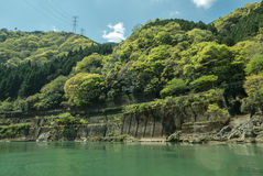 Collines vertes rocheuses par la rivière de Hozugawa images libres de droits